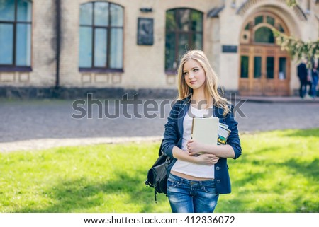 Beautiful, happy young student girl holding book standing with backpack green grass under the tree near the campus, university, school, education. Summer, spring green park, bright sunshine