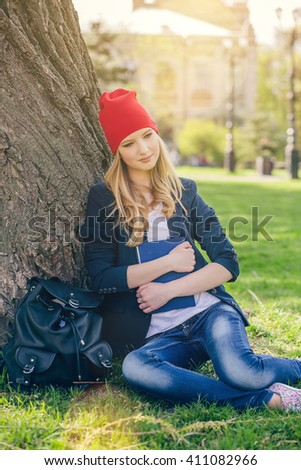 Beautiful, happy young student girl in red hat holding book sitting on green grass under the tree near the campus, university, school, education. Summer, spring green park, bright sunshine