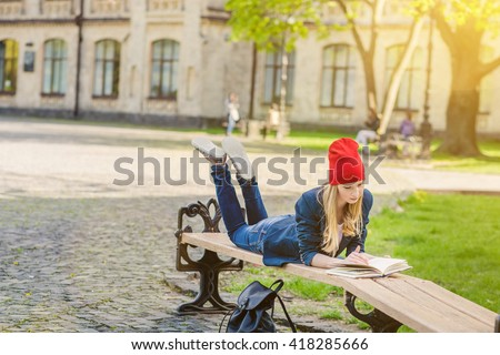 Beautiful, happy young student girl lie down  on green grass near the campus, university, school, education in red hat holding book on the bench, spring green park, bright sunshine - stock photo