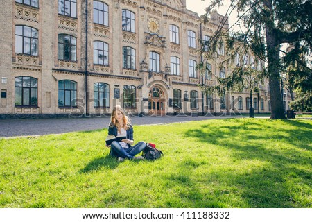Beautiful, happy young student girl sitting on green grass near the backpack, bag under the tree near the campus, university, school, education. Summer, spring green park - stock photo