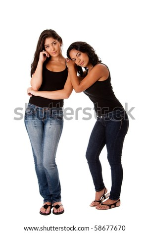 Beautiful happy young woman couple together standing, resting on shoulder, both dressed in black tank top and blue denim jeans, isolated. - stock photo