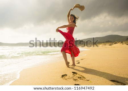 Beautiful happy young woman dancing on a sunny sandy beach - stock photo