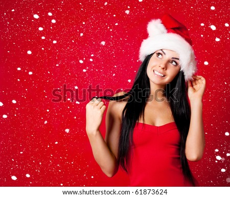 beautiful happy young woman dressed as santa with snow falling on her