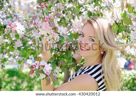 Beautiful happy young woman in a flowering spring garden - stock photo
