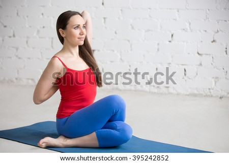 Beautiful happy young woman in bright colorful sportswear working out indoors in white loft interior. Girl sitting in Gomukhasana, Cowface posture on blue mat. Yin yoga Shoelace pose. Full length - stock photo