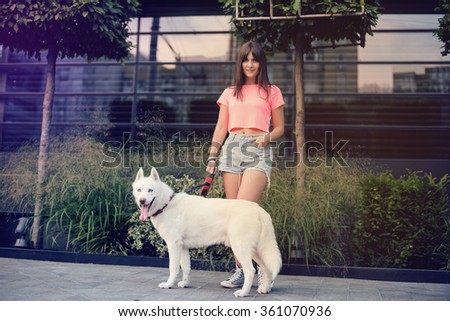 beautiful happy young woman in shorts with white husky dog - stock photo