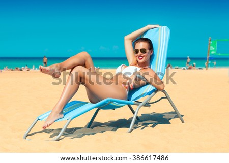 beautiful happy young woman in white bikini and sunglasses relaxing in deck chair on the sand beach