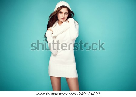beautiful happy young woman in white warm long turtleneck sweater, winter cap. Fashionable clothes - stock photo