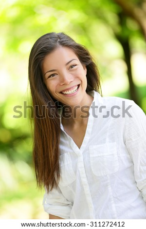 Beautiful happy young woman looking away. She is with long brown hair. Mixed race Asian / Caucasian female is in casuals at park. - stock photo