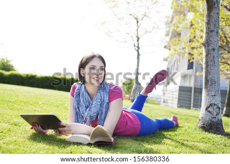 Beautiful happy young woman sitting on grass, enjoy sunny day and listening music with headphones and using digital tablet while reading book. - stock photo