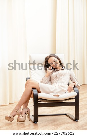 Beautiful happy young woman talking on the phone. She is at home in a comfortable chair. - stock photo