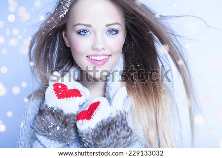Beautiful happy young woman wearing winter gloves covered with snow flakes. Christmas snowing portrait concept.  - stock photo