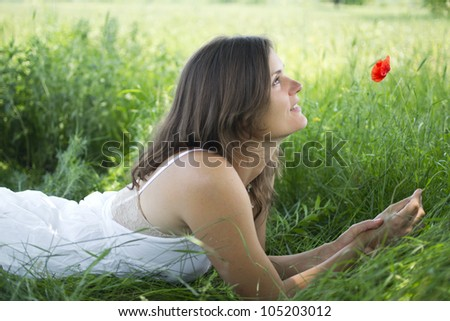 Beautiful happy young woman with a poppy in a meadow - stock photo
