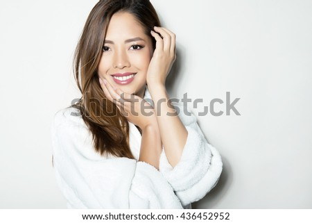 beautiful, happy young woman with flawless skin and long hair posing in bath robe