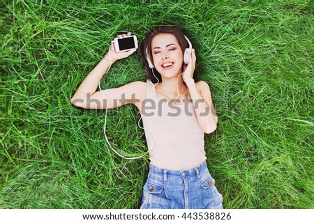 Beautiful happy young woman with headphones listening music lying on grass - stock photo