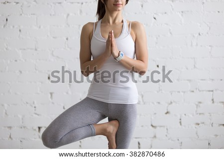 Beautiful happy young woman with smart watch working out indoors, doing yoga exercise, standing in Vrksasana Posture, Tree Pose, full length, close-up - stock photo