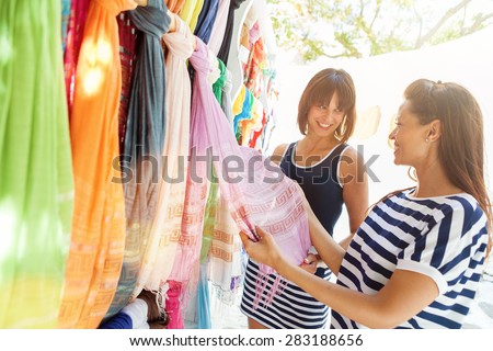 Beautiful, happy young women walking through the streets of Mykonos , looking and choosing clothes,gifts in the street markets.Shopping and vacation theme - stock photo