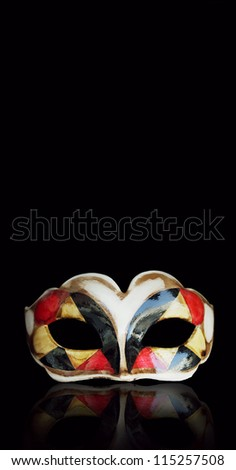 Beautiful Harlequin mask with its reflection above isolated on black background