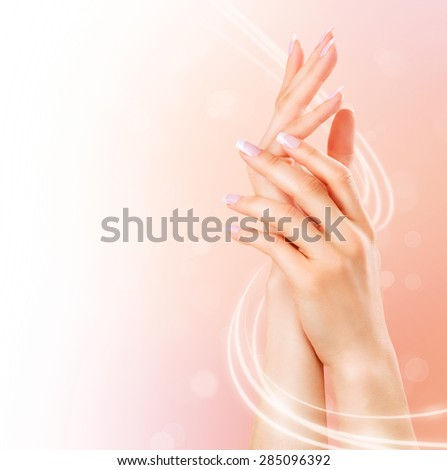 Beautiful Healthy Female Hands. Spa and Manicure concept. Woman hands with french manicure. Soft skin, skincare concept. Beauty nails. over beige background - stock photo