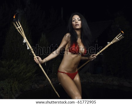 Beautiful healthy fit woman wearing red bikini & Holding burning torches. Night filming. - stock photo
