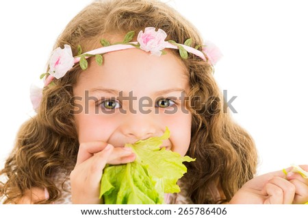 Beautiful healthy little curly girl enjoying eating a lettuce isolated on white - stock photo
