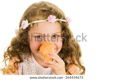 Beautiful healthy little curly girl enjoying playing with a carrot in front of her nose isolated on white