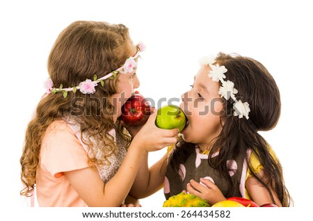 Beautiful healthy little girls feeding each other delicious fresh fruits isolated on white - stock photo