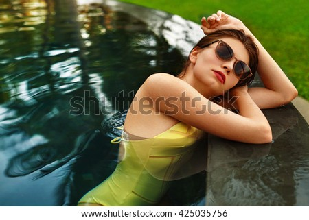 Beautiful Healthy Sexy Woman With Fit Body In Fashionable Elegant Yellow Bikini Swimsuit Relaxing In Swimming Pool Water. Beauty Girl Enjoying Travel Vacation At Resort Spa Hotel. Summer Relax Concept - stock photo