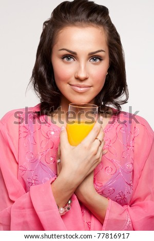 Beautiful healthy woman holding glass of orange juice in hands - stock photo