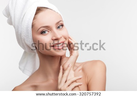 Beautiful healthy woman is satisfied with her body. She is standing with towel on her head and smiling. The lady is touching face and looking at camera happily. Isolated  - stock photo