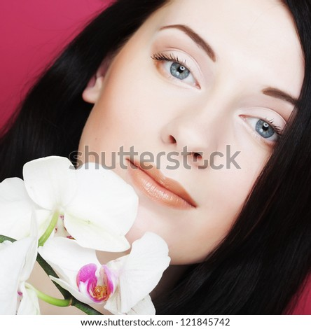 Beautiful healthy woman with orchid flower. Over pink background. - stock photo