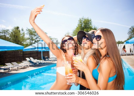 Beautiful healthy women are making selfie. They are standing near a swimming pool and smiling. The friends are drinking cocktails and embracing - stock photo