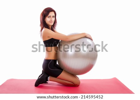 Beautiful healthy young girl with a fitness ball on a white background.