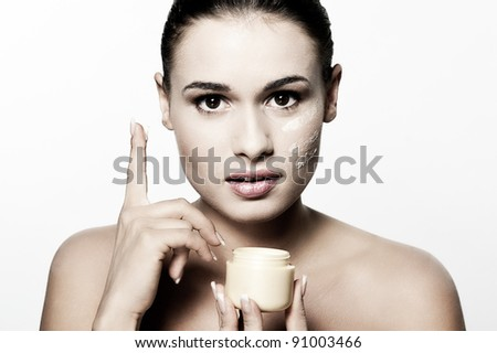 Beautiful healthy young woman applying facial moisturizing creme - stock photo