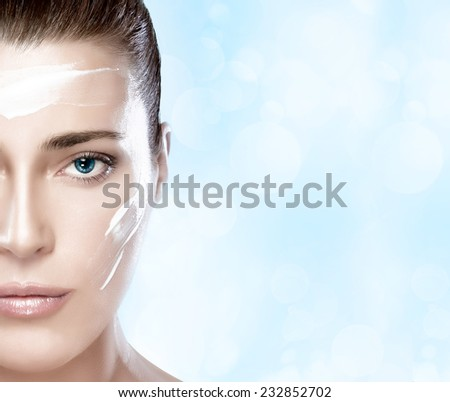Beautiful healthy young woman with moisturizer on her cheek and forehead. Half face close-up portrait. Skin care concept. Spa Treatment - stock photo