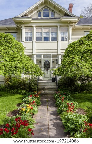 Beautiful heritage home with a lovely green front yard in spring. - stock photo