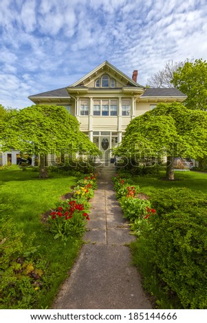 Beautiful heritage home with flowering tulips in a spring garden. - stock photo