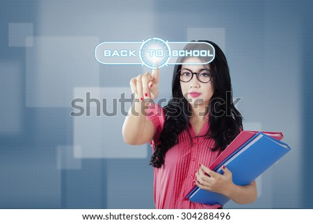 Beautiful high school student using futuristic interface and pressing the button of back to school - stock photo
