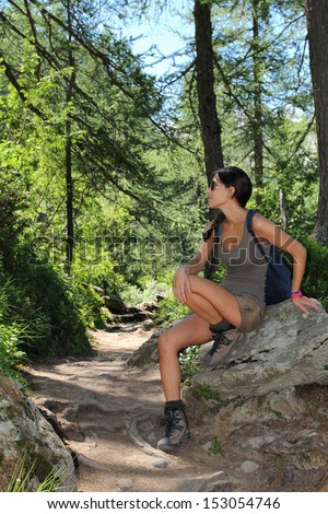 Beautiful hiker girl posing on a rock in the forest