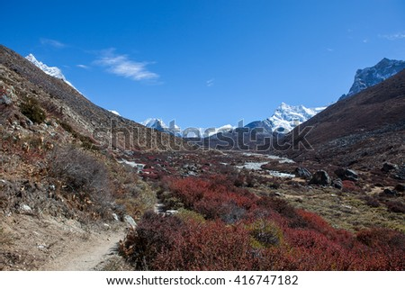 Beautiful Himalayan landscape with mountain range on the horizon and barberry shrubs in the valley on foreground. View over the range of mountain peaks in snow and rocky valley on a bright sunny day. - stock photo