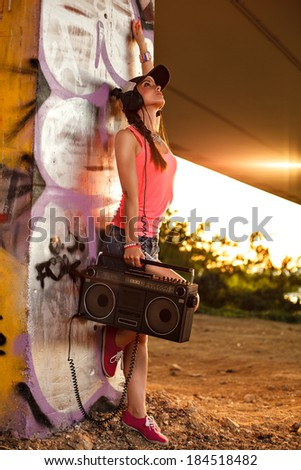 Beautiful hip hop woman wearing cap with a tape recorder and headphones leaning against the wall and enjoying the music - stock photo
