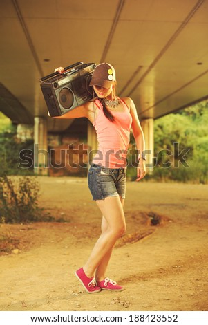 Beautiful hip hop woman with a cap which holding a tape recorder on shoulder - stock photo