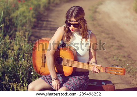Beautiful hippie girl alone on the countryside road - stock photo