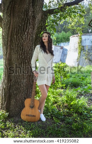 Beautiful hippie girl alone on the countryside standing near tree with guitar - stock photo