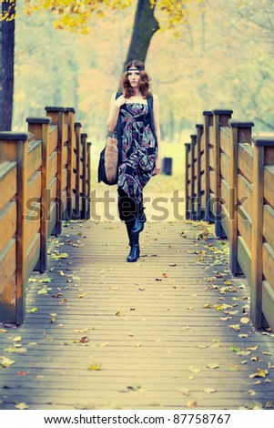 Beautiful hippie girl fashionalby posing on a wooden bridge in autumn scenery wearing maxi long dress and gorgeous make up. - stock photo