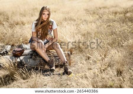 Beautiful hippie girl sitting on a tree stump - stock photo
