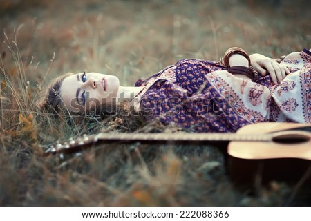 Beautiful hippie girl with guitar lying on the grass - stock photo