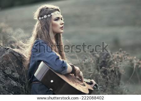Beautiful hippie girl with guitar sitting on grass near stone - stock photo