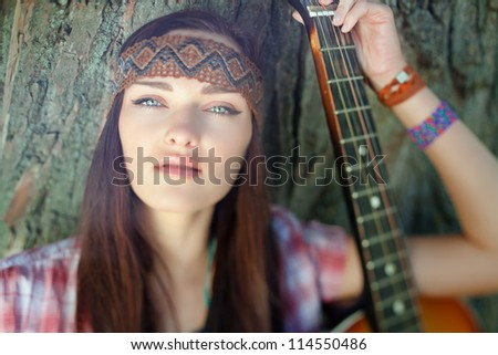 Beautiful hippie girl with guitar. Tilt-shift effect. - stock photo