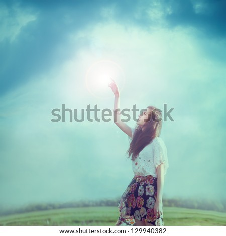 beautiful hipster girl dreams to touch the sun - stock photo